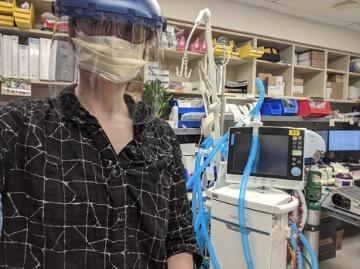 Shira Epstein in face shield and mask in foreground with ventilator cable prototype in background